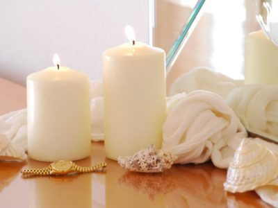 Close look of candles and a golden wrist watch on a desk beside a mirror giving a sense of relaxation